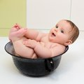 Baby taking bath little in vintage washing up bowl Stock Photo