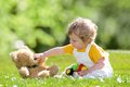 Baby with teddy bear on a summer meadow Royalty Free Stock Photos