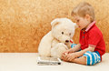 Baby and teddy with touch pad bear at home Stock Photography