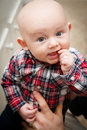 Baby with thumb in mouth happy big blue eyes wide open a finger his looking upward wearing a plaid shirt Stock Photo