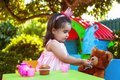 Baby toddler girl playing in outdoor tea party feeding her best friend Teddy Bear with candy Royalty Free Stock Photo