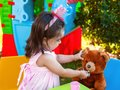 Baby toddler girl playing in outdoor tea party feeding her best friend Teddy Bear with candy gummy Royalty Free Stock Photo