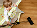 Baby with vacuum cleaner Royalty Free Stock Image