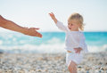 Baby walking to mothers outstretched hands Royalty Free Stock Photography