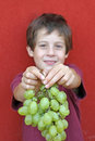 Baby who kindly offers grapes a bunch of white Royalty Free Stock Photos