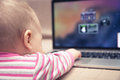 Baby working on laptop computer with hand reaching to touchpad Royalty Free Stock Photo