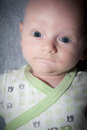 Baby with worried expression boy gray and green outfit lying on his back on a gray blanket blue eyes Royalty Free Stock Photography