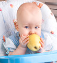 Baby with yellow apple newborn Stock Photos