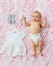 Baby girl in diaper lying with dress on blanket Royalty Free Stock Photo