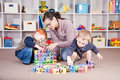 Babysitter playing kids block game with children Royalty Free Stock Photo