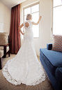 Back of bride at window wearing lace wedding dress a Stock Photography