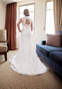 Back of bride at window wearing lace wedding dress in hotel suite Stock Photos
