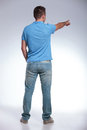 Back of a casual man pointing view young away from the camera on gray background Royalty Free Stock Images