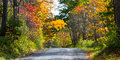 Back country road in autumn dips down a hill bright upstate new york landscape Royalty Free Stock Photography
