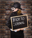 Back of a funny looking headmaster holding black board with back to school written in chalk school brick wall background Royalty Free Stock Photos