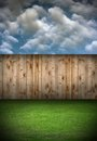 Back garden with wooden fence and green fresh turf under cloudy sky Royalty Free Stock Image