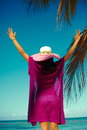 Back of glamor sexy model girl in colorful cloth and sunhat high fashion look behind blue beach ocean water Royalty Free Stock Photography
