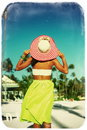 Back of glamor sexy model girl in retro style with palms high fashion look colorful cloth and sunhat behind blue beach sky Stock Images