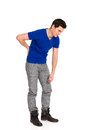 Back pain backache young man in blue shirt holding lower in full length studio shot on white Stock Images