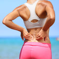 Back pain woman having injury in lower back painful muscle fitness girl sport girl with sports outdoor on beach Royalty Free Stock Images