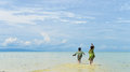Back portrait of two native young sisters running and jumping in the shallow water on tropical beach. Royalty Free Stock Photo
