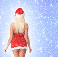 Back of a sexy blond woman in santa lingerie on snow young and posing the image is taken light blue snowy background Stock Images