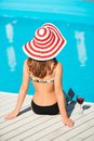 Back shot of young woman sitting close by swimming beautiful pool with wine glass at hot summer day Royalty Free Stock Photos