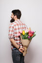 Back side of Handsome young man with beard  and nice bouquet of flowers Royalty Free Stock Photo