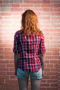 Back side view of a redhead female befor red brick wall Stock Photos