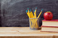 Back to school background with books, pencils and apple over chalkboard Royalty Free Stock Photo
