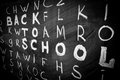 Back to school background with title `Back to school` among other letters of English alphabet written by white chalk Royalty Free Stock Photo
