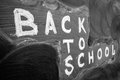 Back to school background with title `Back to school` written by white chalk on the black chalkboard