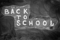 Back to school background with title `Back to school`  written by white chalk on the black chalkboard and chalky stains Royalty Free Stock Photo