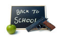 Back to school blackboard sign with an apple and a mm handgun signifying arming teachers Royalty Free Stock Images