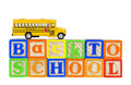 Back to school bus blocks spelled out in wooden alphabet with miniature yellow on top Royalty Free Stock Images