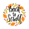 Back to school. Calligraphic phrase on autumn season background. Vector lettering