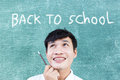 Back to school concept asian teenager looking up with behind green chalkboard and text for education background Royalty Free Stock Photos