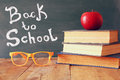 Back to school concept. Blackboard with books, apple and glasses Royalty Free Stock Photo