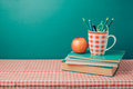 Back to school concept with  books, pencils and apple on tablecloth Royalty Free Stock Photo