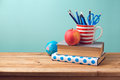 Back to school concept with books, pencils in cup, apple, and globe Royalty Free Stock Photo