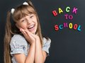 Back to school concept photo of adorable young cheering girl looking at camera at the black chalkboard in classroom Royalty Free Stock Images