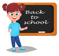Back to school. Cute girl standing near blackboard. Pretty littl