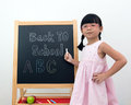 Back to school little asian girl in front of the blackboard pointing Royalty Free Stock Images