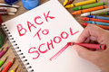 Back to school message reminder, child writing with pencil Royalty Free Stock Photo