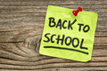 Back to school reminder handwriting on a green sticky note against grained and knotted wood board Stock Image