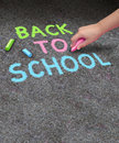 Back to school sidewalk chalk drawing with blank area for copy space on a concrete with the hand of a child holding a color as a Royalty Free Stock Images