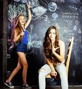 Back to school after summer vacations, two teen girls in classroom with blackboard painted Royalty Free Stock Photo