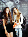 Back to school after summer vacations, two teen real girls in classroom with blackboard painted together, lifestyle