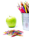Back to school supplies with color pencils in pencil holders on and apple white background Royalty Free Stock Photo