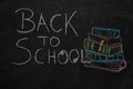 Back to school text and stack of books with apple drawn on black chalkboard Royalty Free Stock Photo